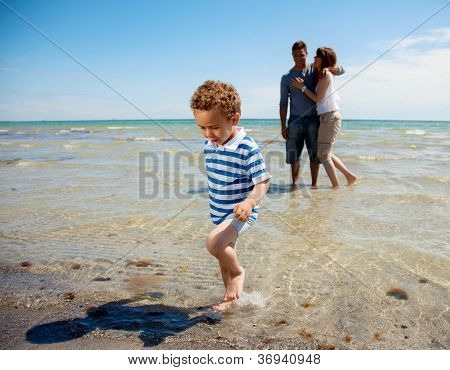 Young Couple Watches As Son Walks Away From The Water