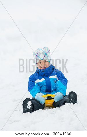 Boy goes for a drive on a snow slope.