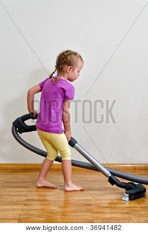 Cute Little Girl Cleaning Floor With Vacuum Cleaner