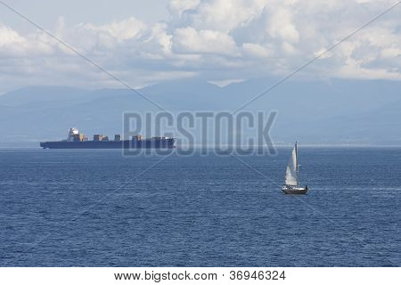 Sailboat And Freighter By Alaskan Mountains