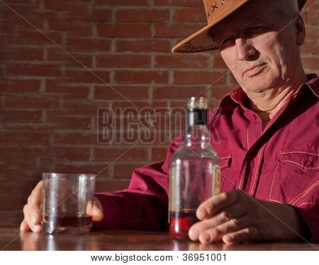 Caucasian old male with a nice bottle sitting
