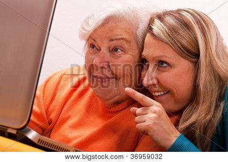 Female Senior With Laptop Is Having Fun