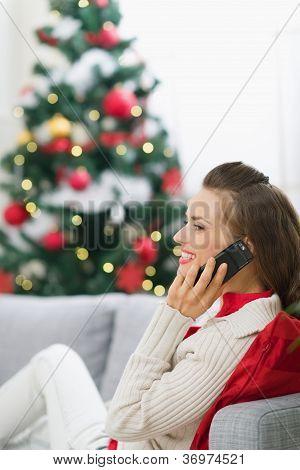 Jovem feliz perto de árvore de Natal, fazer chamada de telefone