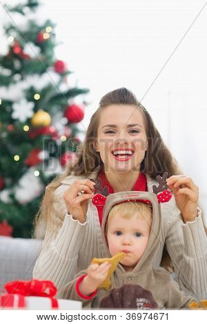 Mother Playing With Baby Near Christmas Tree