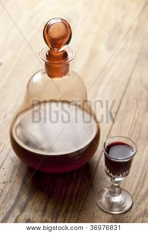 Decanter with glass of liqueur.