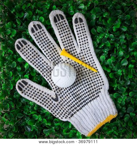 golf ball hand gloves and yellow tee