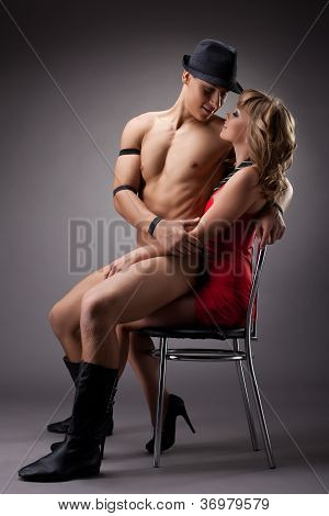striptease playful man sit on sexy girl in red