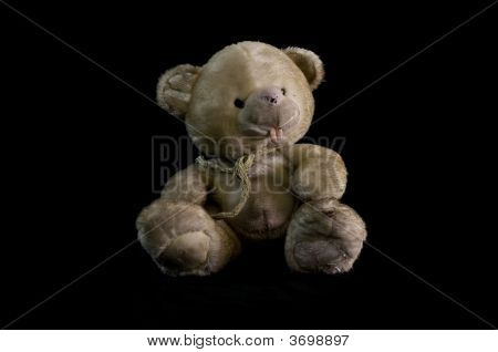Old Teddy Bear Toy On Black Background