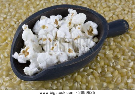 Wooden Scoop Of Popcorn And Corn Kernels