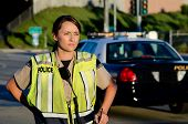 stock photo of lightbar  - A female police officer staring and looking serious during a traffic control shift - JPG