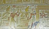 stock photo of horus  - Ancient Egyptian bas relief carving showing the Pharaoh Seti I holding his flail of office before the god of the underworld Osiris with the falcon headed god Horus behind him.  Abydos Temple, Egypt.