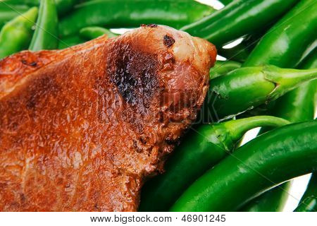 meaty food : grilled red meat steak over green hot chili peppers on a white back background