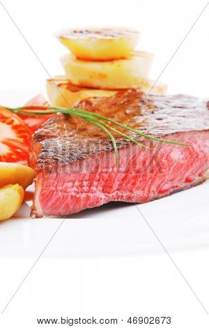 meat food : roasted fillet on white plate with tomatoes and chives isolated over white background