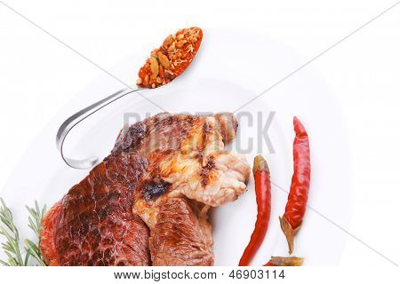 meat food : roasted steak on white plate with red thin chili pepper and spices isolated over white background
