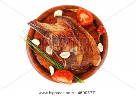 hot red beef meat steak on red wooden plate with capers and tomatoes isolated over white background
