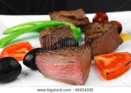 meat savory : grilled beef fillet mignon on white plate with tomatoes apples and pepper over black wooden table