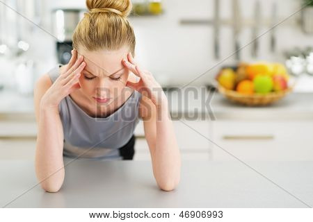 Portrait Of Stressed Young Housewife In Modern Kitchen