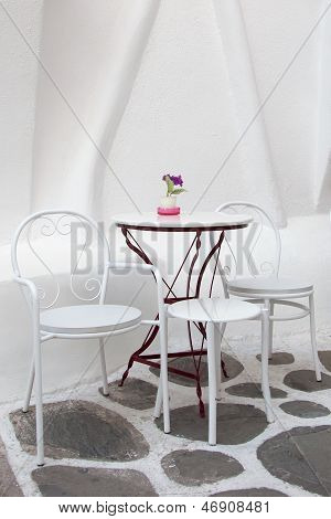White Table And Chairs In The Cafe With Flowers On The Street In The Greek Town
