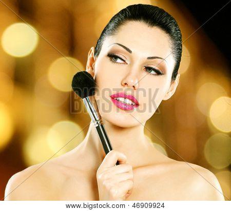 Aplicar o blush no rosto de mulher bonita