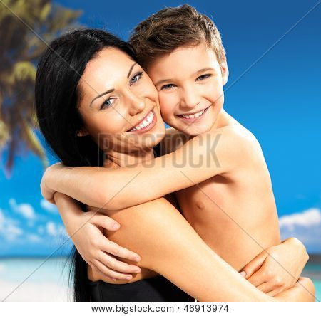 Happy Smiling Mother Hugs Son At Tropical Beach