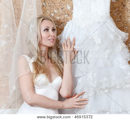 The young woman with a wedding dress in hands dreams of wedding