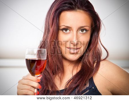 Portrait of young happy smiling cheerful beautiful woman with glass of red wine. She is this year's world champion in shooting.