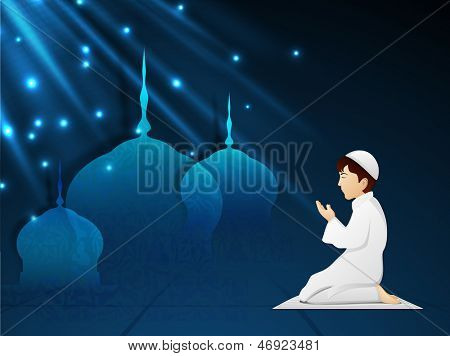 Little Muslim boy in traditional dress praying (reading Namaz, Islamic Prayer) with shiny view of mosque on blue background.