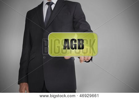 Businessman selecting green tag with the word agb written on it on greybackground