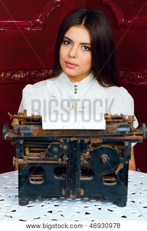 Young beautiful woman typing a letter with antique typewritter