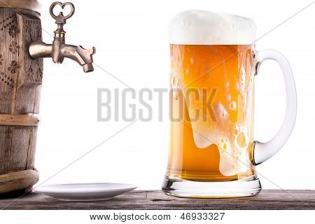 Glass Of Beer With Barrel On A Wooden Table