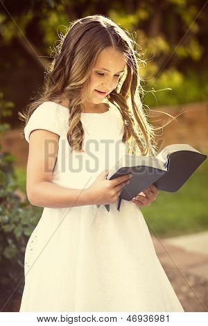 Cute little girl reading the Bible