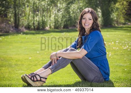 Beautiful woman relaxing outdoors on the grass
