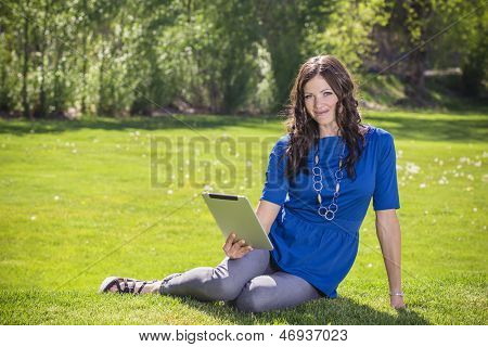 Beautiful woman using a tablet PC outdoors