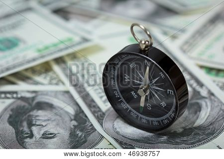 Closeup Of A Compass Placed On U.s. Dollar Banknotes