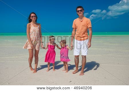 Young Nice Family With Two Kids Walking At Beach