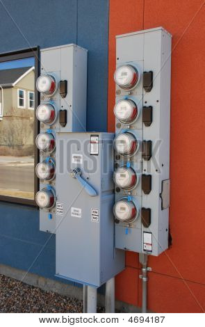 Gray Utility Meters Against A Stucco Wall