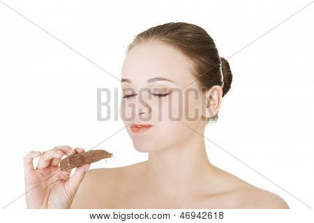 Beautiful woman biting a chocolate bar. Isolated on white