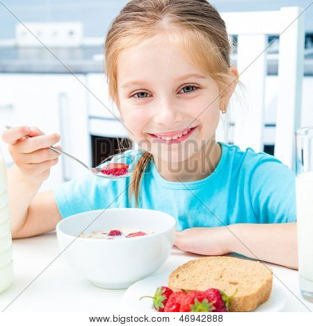 cute little girl eating cereal and strawberries in the kitchen