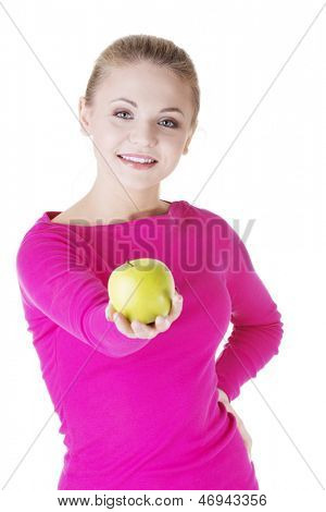 Young woman holding green fresh apple in hand, isolated over white background
