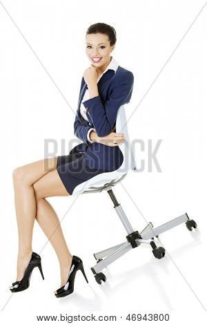 Beautiful successful businesswoman sitting on ofice chair and smiling, isolated on white