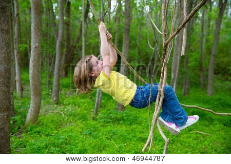 children girls playing hanging and climbing from lianas at the jungle forest park outdoor