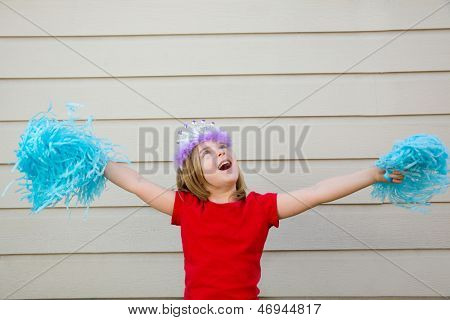 Blond kid girl playing like cheerleading pom poms with princess crown