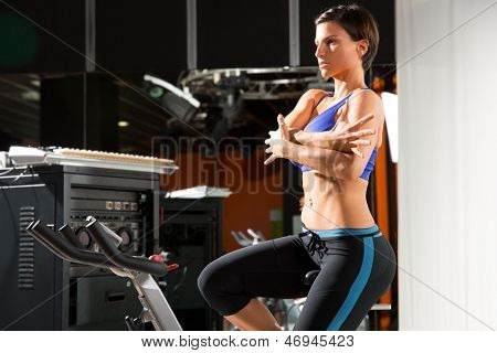 Aerobics spinning monitor trainer woman stretching exercises after workout at gym