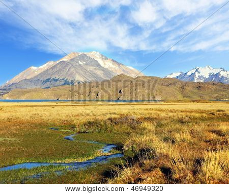The huge valley surrounded by snow-capped mountains. Crosses the picturesque valley of the creek. The solitary Estancia in the national park Perito Moreno in Argentina.