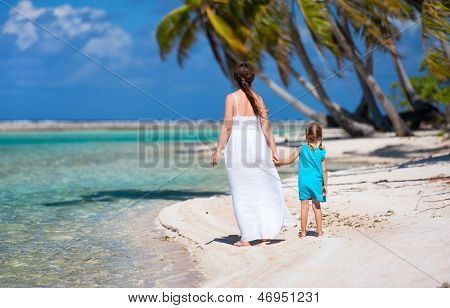 Back view of mother and daughter on a deserted island