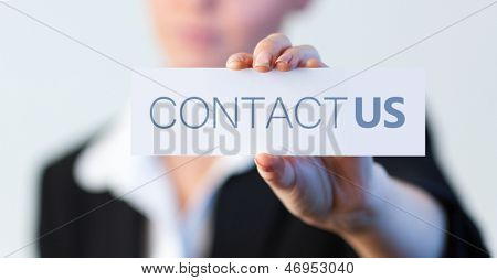Businesswoman holding a label with contact us written on it with focus on her hand