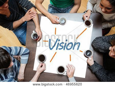 Team brainstorming over a poster on a table with vision written on it