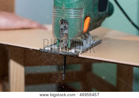 Close Up Image Of An Electric Jigsaw Cutting Sheets On A Wooden Plank