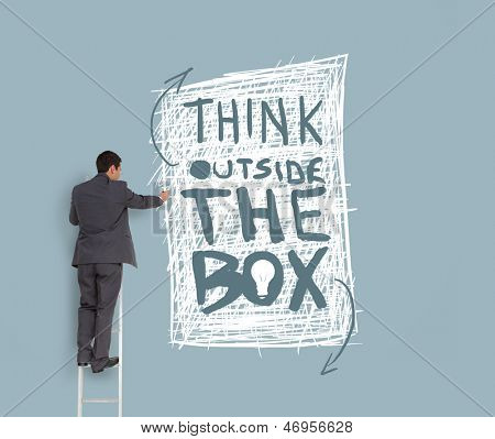 Businessman drawing think outside the box message on grey wall