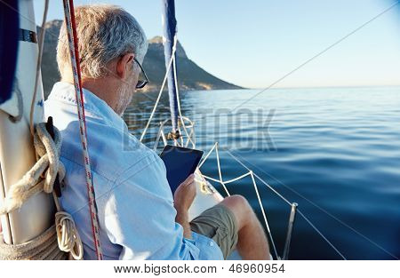 sailing man reading tablet computer on boat with modern technology and carefree retired senior successful lifestyle